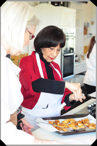 Darina Allen watches as Madhur Jaffrey seasons potatoes for Aloo Gobi